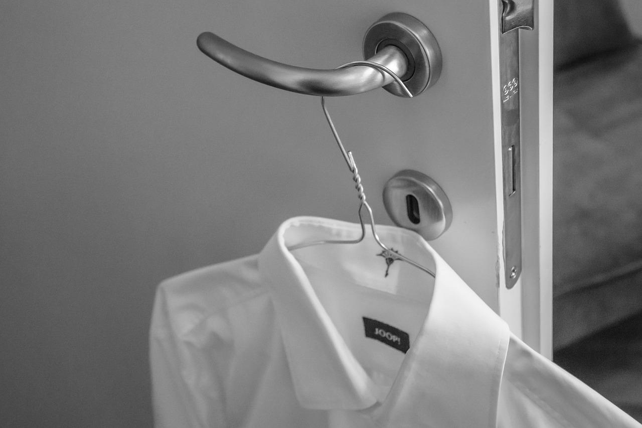 Белая рубашка на плечиках на ручке двери