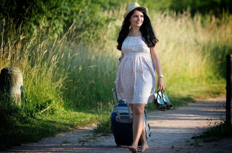 Девушка с чемодан идет по сельской дороге с туфлями в руках