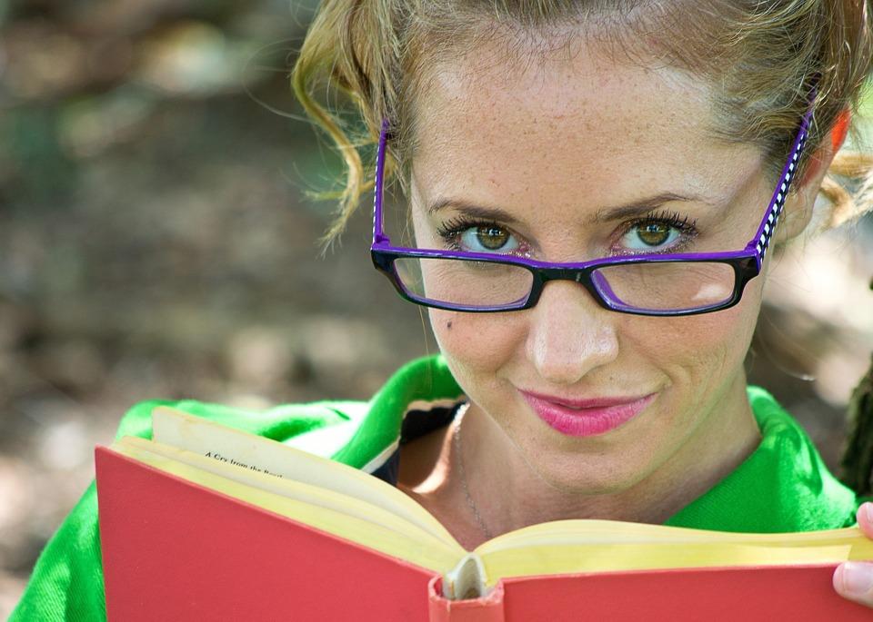 Девушка в очках читает книгу
