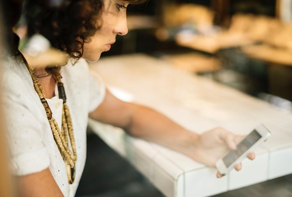 Женщина смотрит на смартфон в ожидании