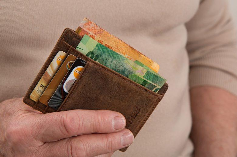 Кошелек в руках, денежные купюры