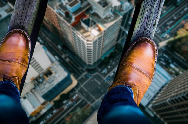 Человек идет по узкой планке на высоте