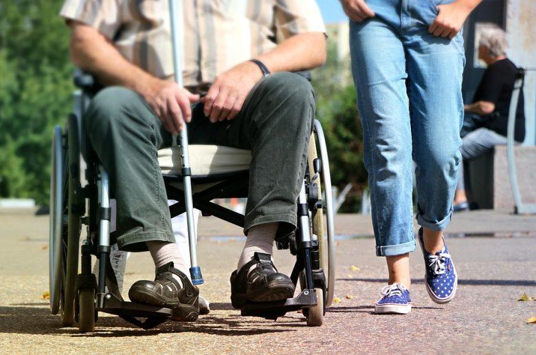 Человек в инвалидном кресле и рядом с ним волонтер