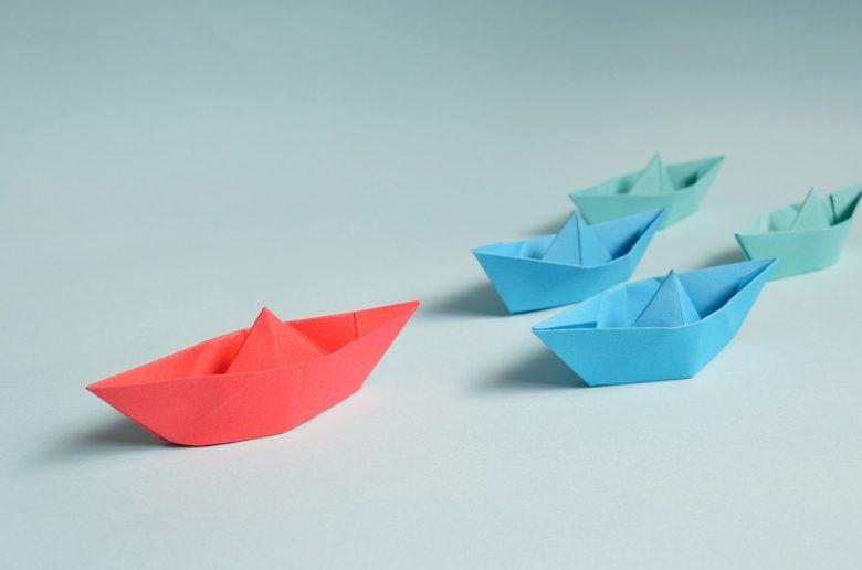 Несколько бумажных корабликов на столе; один, более крупный, впереди.
