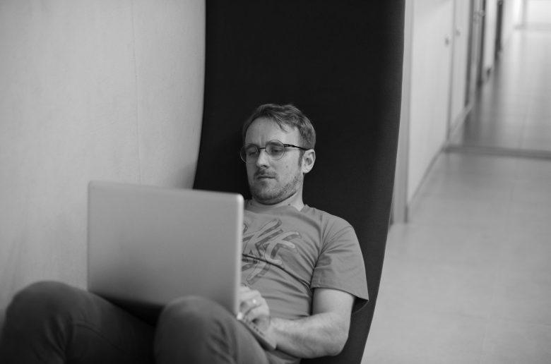 Молодой человек полулежит в офисном кресле с ноутом на коленях.