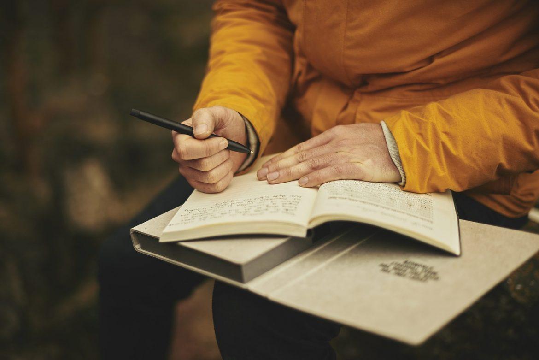 Пожилая женщина пишет в блокноте
