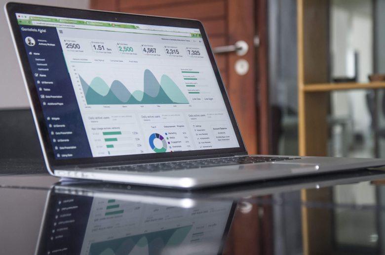 На столе компьютер, на мониторе - статистика, графики, диаграммы.