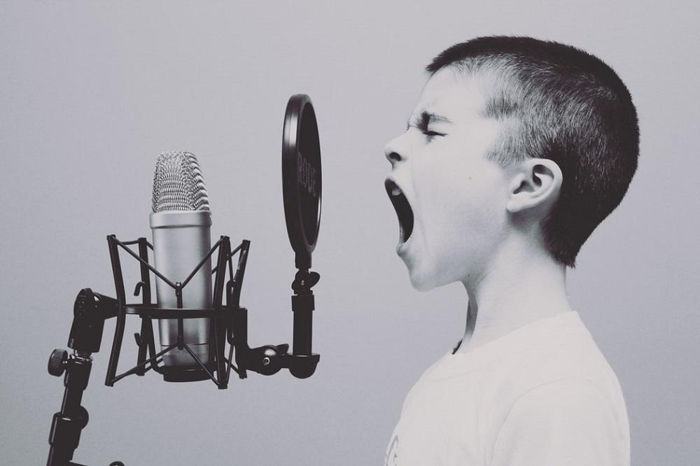 Мальчик что-то кричит в микрофон