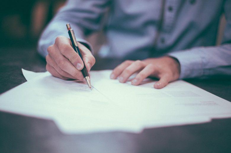 Молодой человек подписывает договор