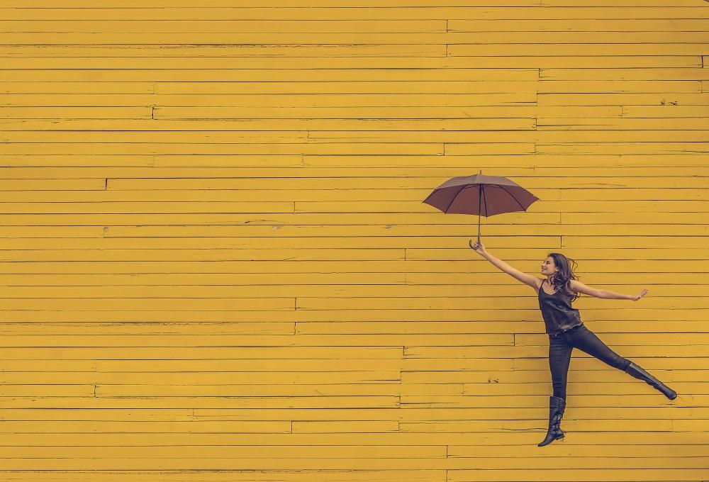 Девушка с зонтиком на фоне стены, как будто летит