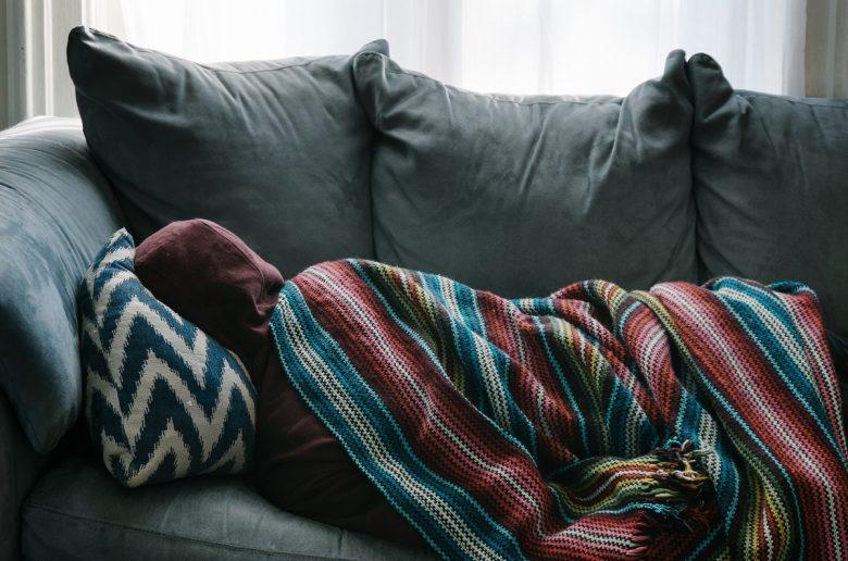 Человек на диване, спит, завернувшись в одеяло, натянув на голову капюшон