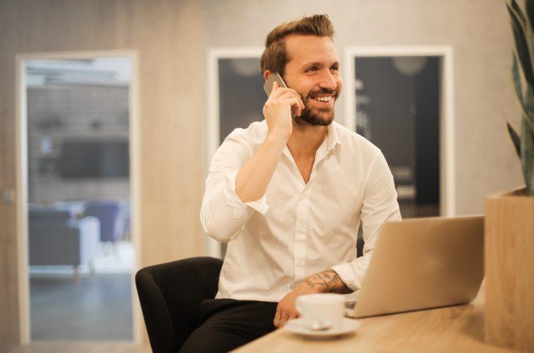 Молодой мужчина за столом в деловой обстановке, говорит по телефону, на столе - ноутбук