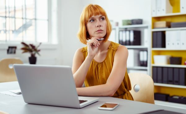 Женщина в желтом платье в офисе за ноутбуком