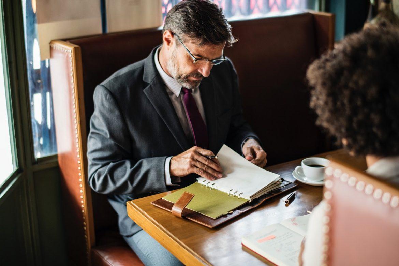Мужчина и женщина беседуют за столом, у мужчины в руках ежедневник, деловая обстановка