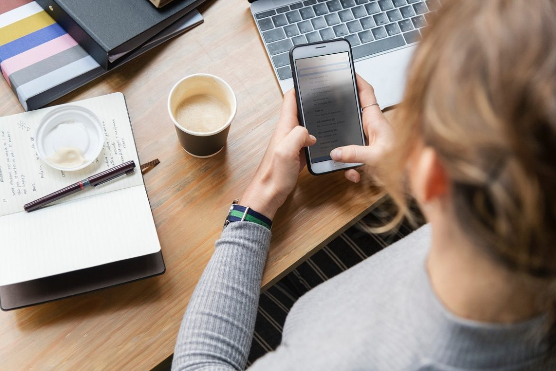 Девушка сидит за столом, в руках смартфон, набирает сообщение