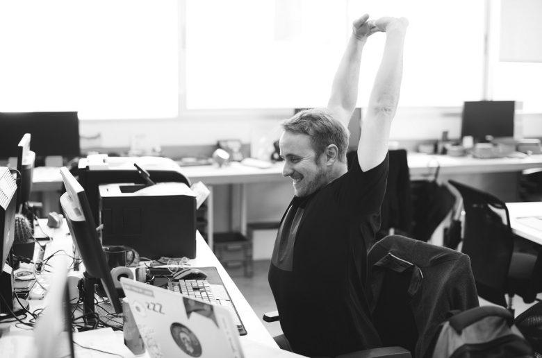 Молодой человек в офисе за столом, тянет руки к потолку, потягивается