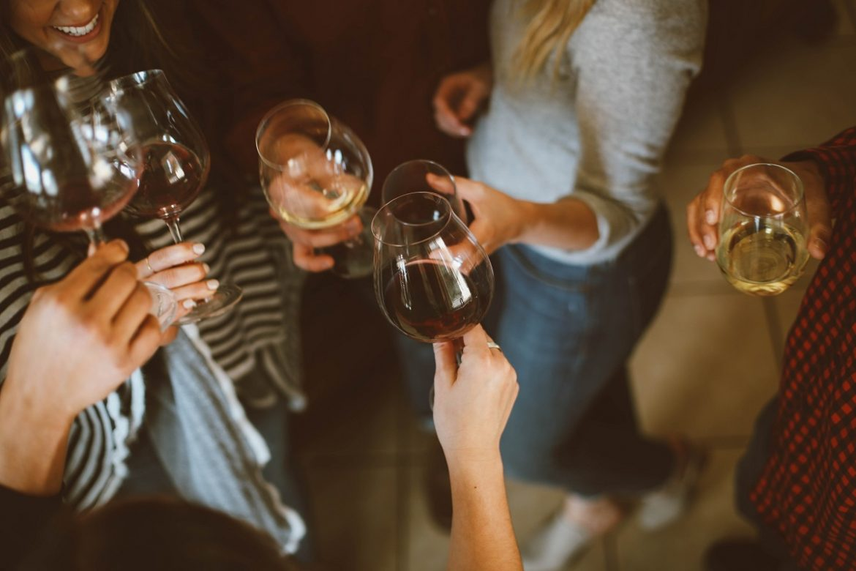 Люди в деловой одежде стоят кругом, в руках - бокалы с вином