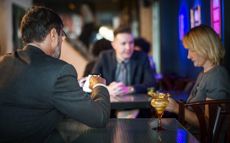 Три коллеги (2 мужчины, 1 женщина) лет сорока что-то обсуждают в деловой обстановке