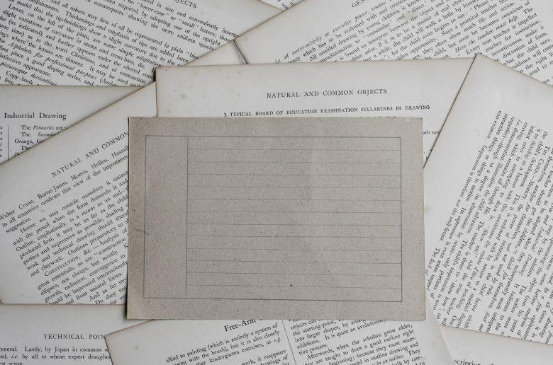 По столу разбросаны тексты на английском, посреди них - белый лист из тетради в линейку