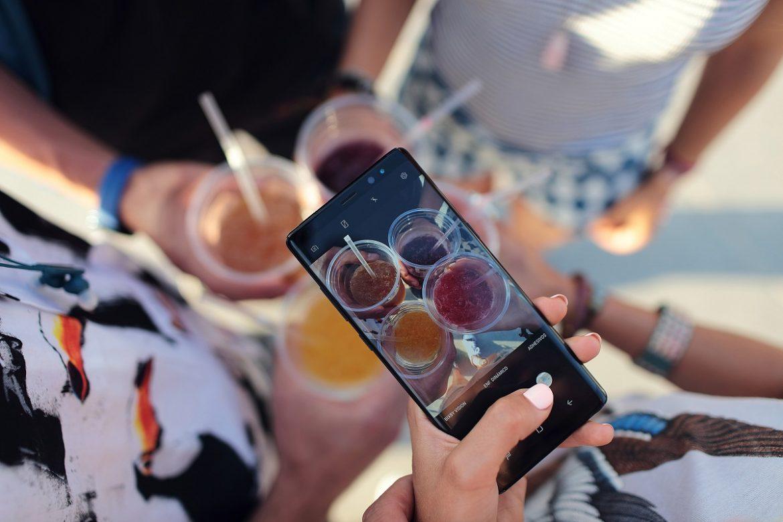 Кто-то снимает на смартфон стол с коктейлями