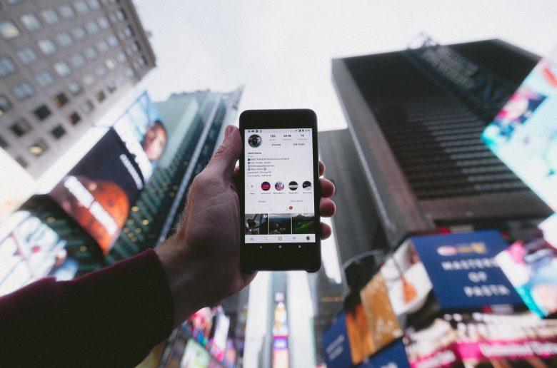 Мужчина держит смартфон на фоне небоскребов