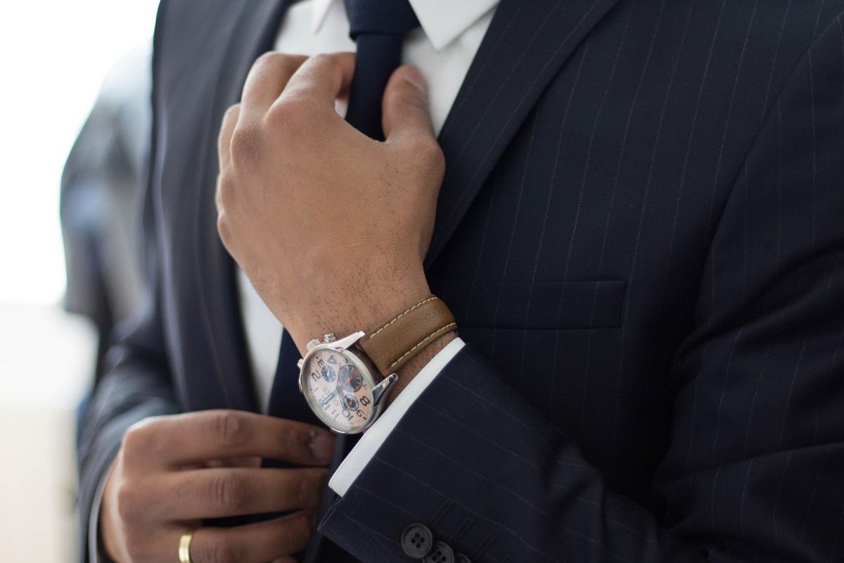 Мужчина в костюме поправляет галстук