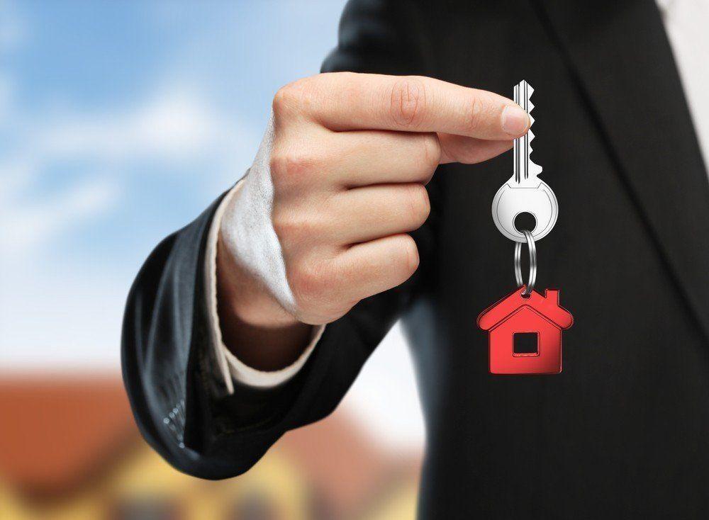 Ключ с брелком в виде домика в руках у мужчины