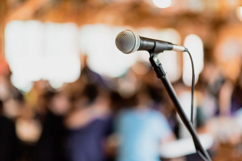 Микрофон на размытом фоне комнаты, наполненной людьми