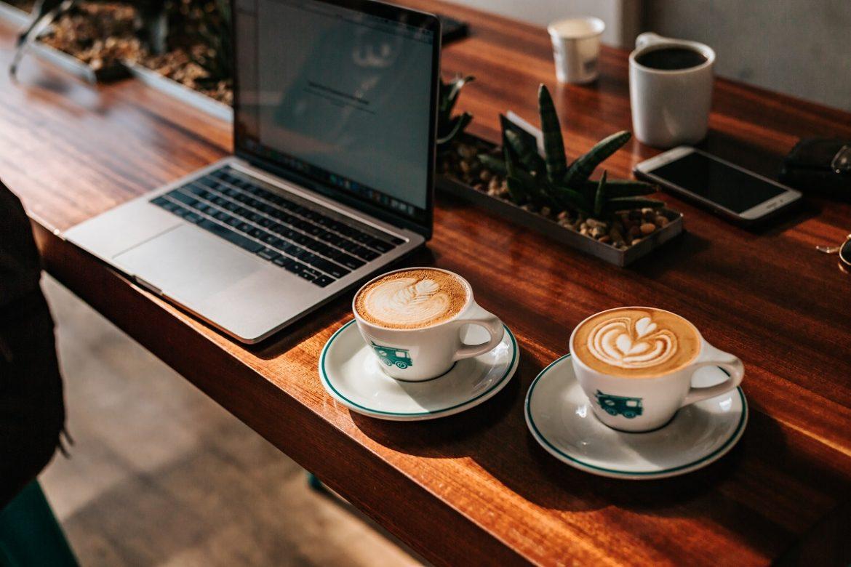 На столе компьютер и две полные чашки кофе