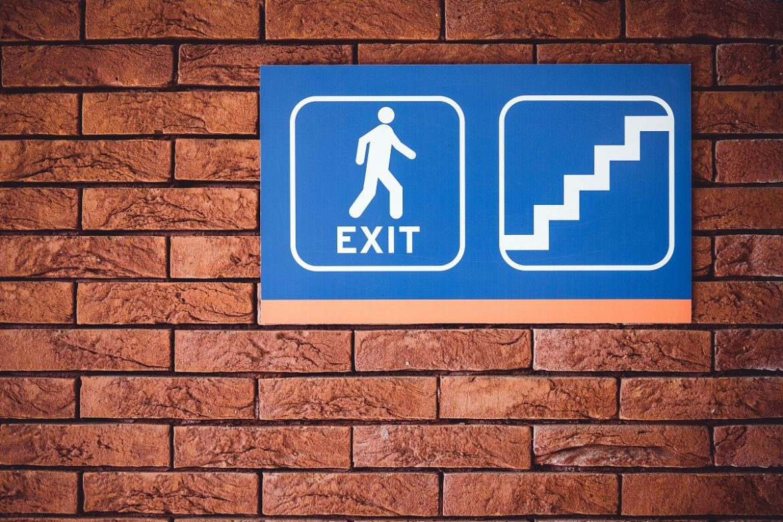 Указатель с надписью Exit на кирпичной стене