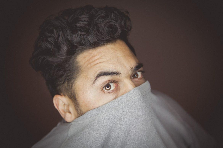 Обличчя молодого чоловіка, який прикрив підборіддя светром