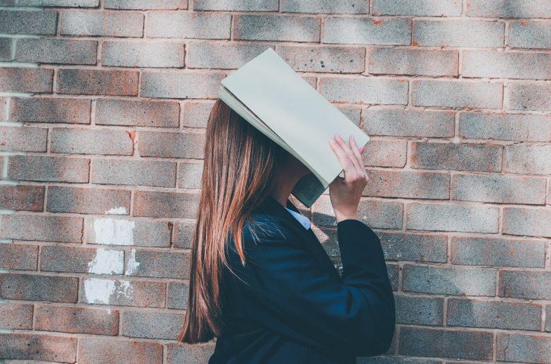 Дівчина прикрила обличчя відкритою книгою